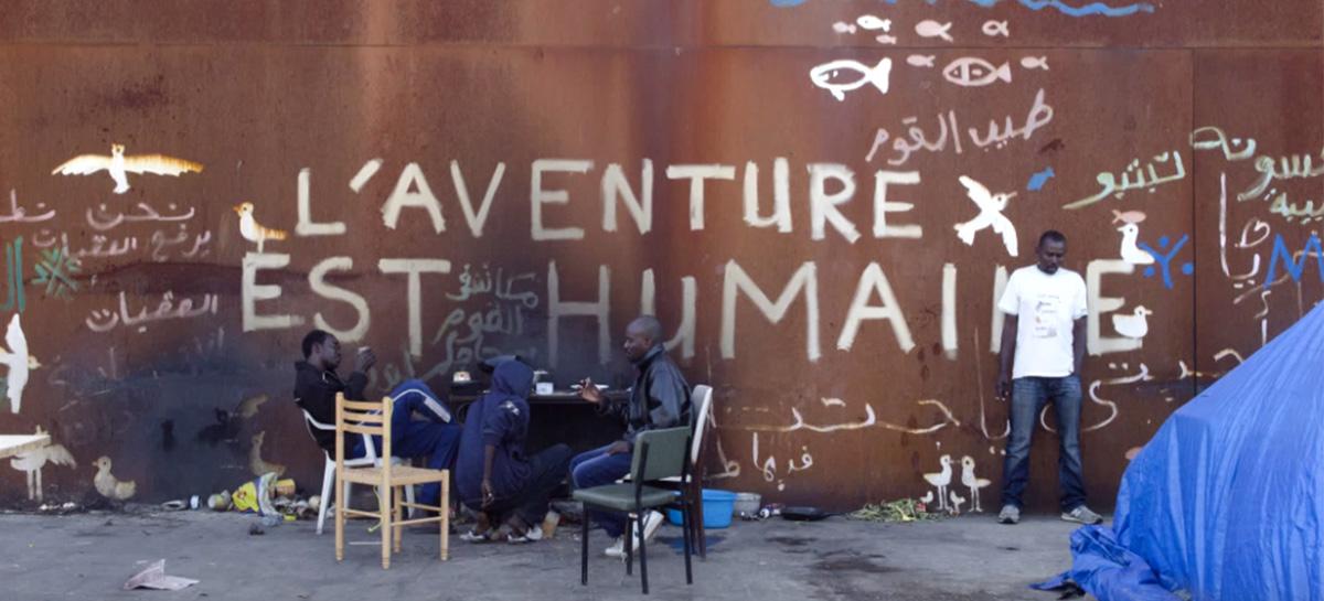 """Réfugiés à Calais devant un slogan """"L'aventure est humaine"""""""